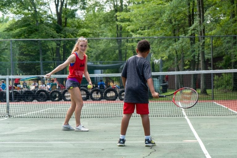 counselor teaching tennis